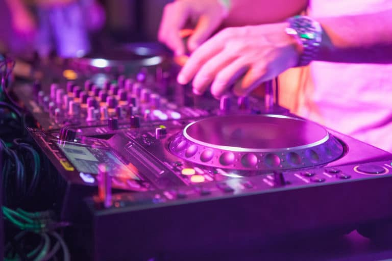 DJ playing music at mixer on colorful blurred background. The hands close up